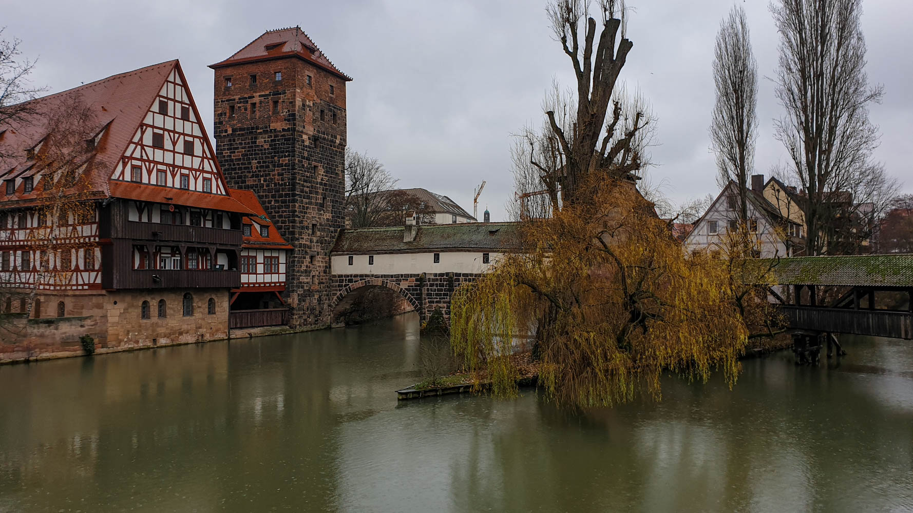 View of a bridge and a couple of red brick buildings with some willow trees in the foregrownd on a cloudy day