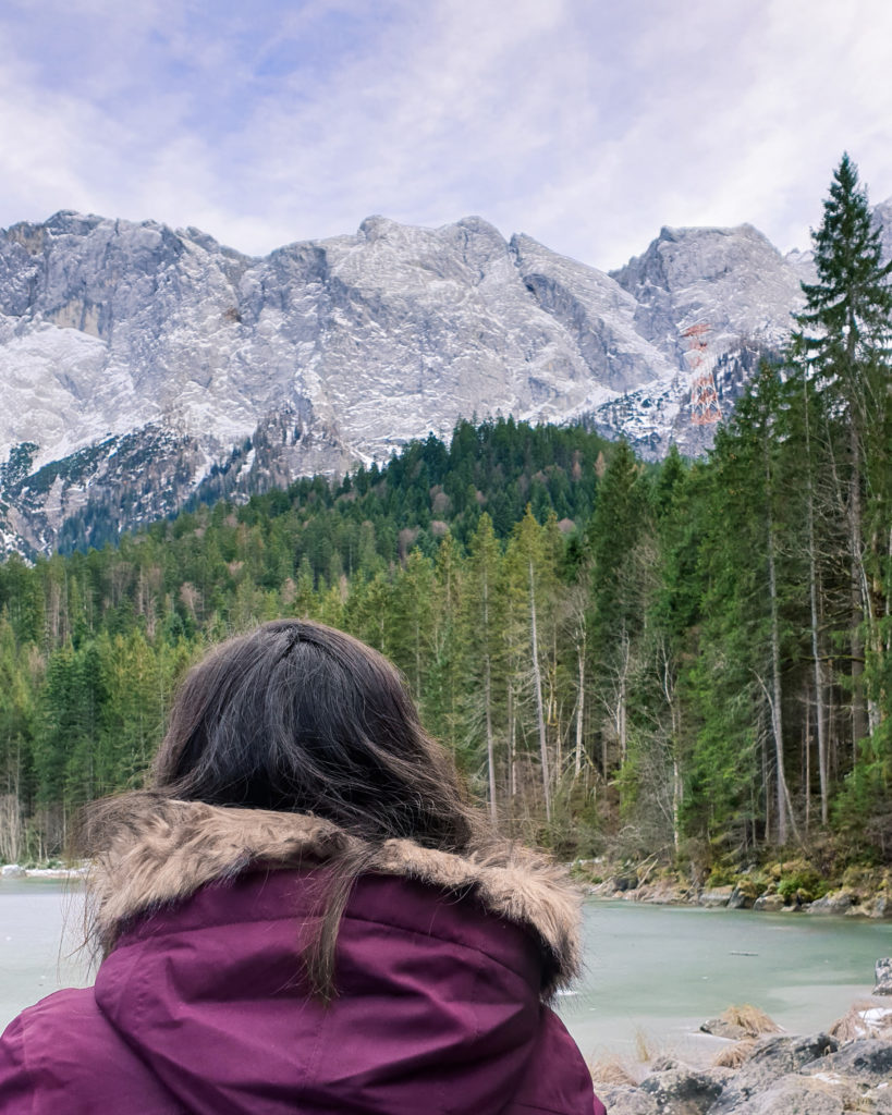 a girl in a mountain scape by a frozen lake, a forest and the outline of a mountain