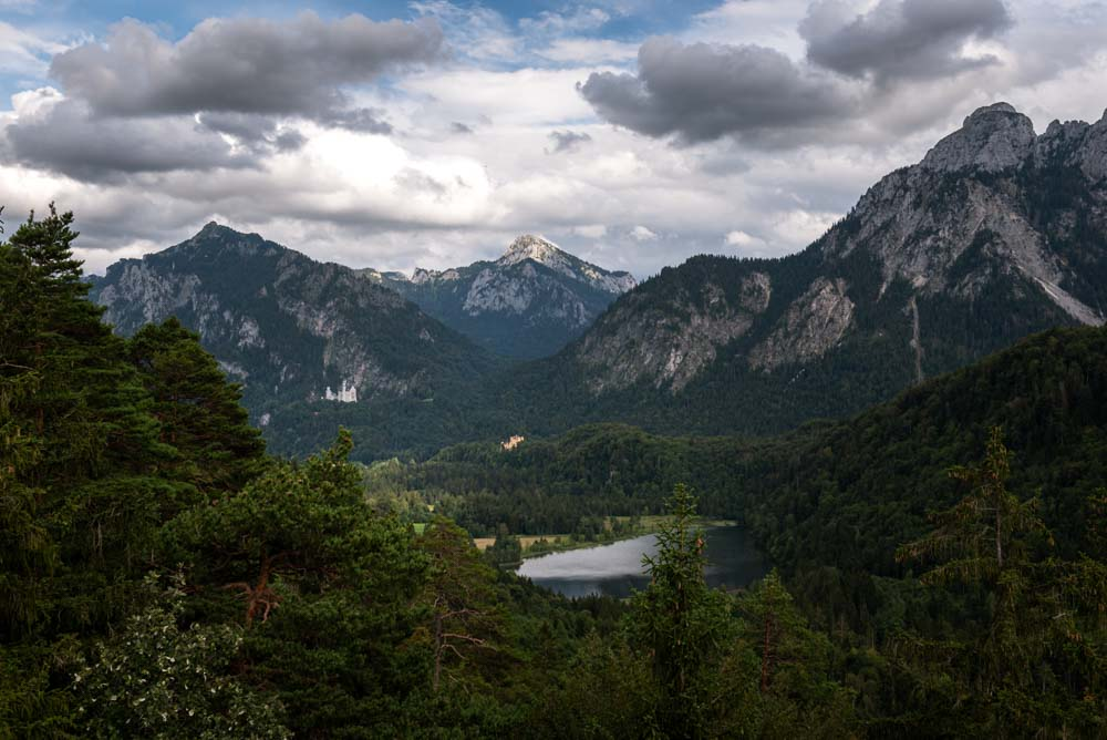 Views from the top of Kalvarienberg while hiking in Füssen. Mountain range with 2 castles and a lake before.