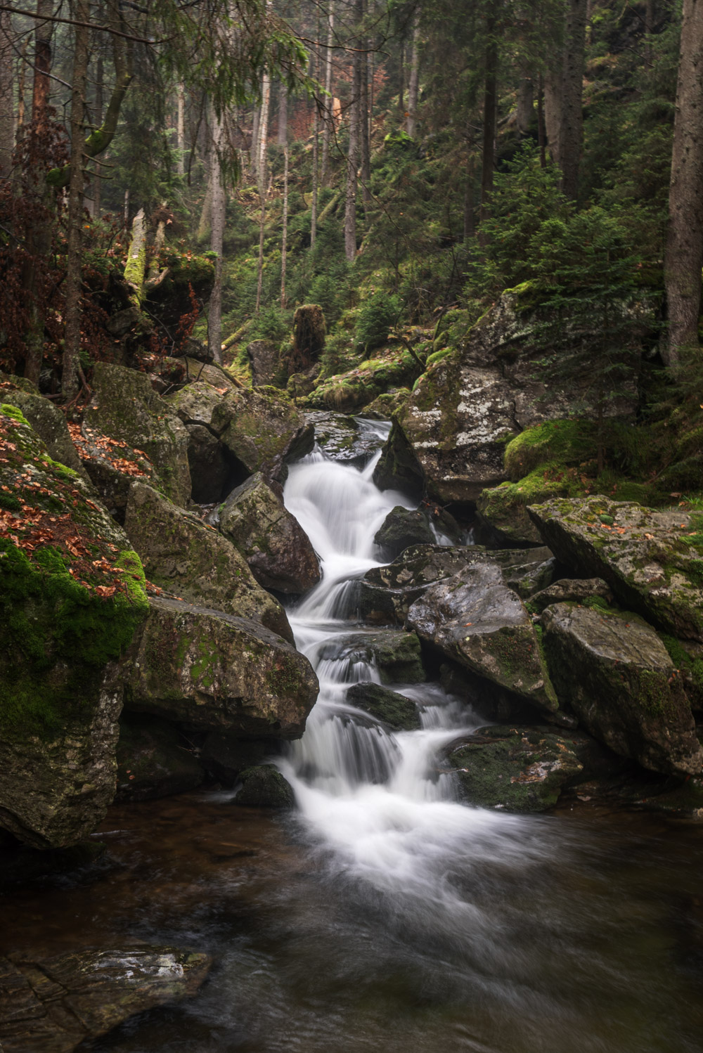 Long exposure of a small waterfall in a lush forest during while winter hiking in Bavaria